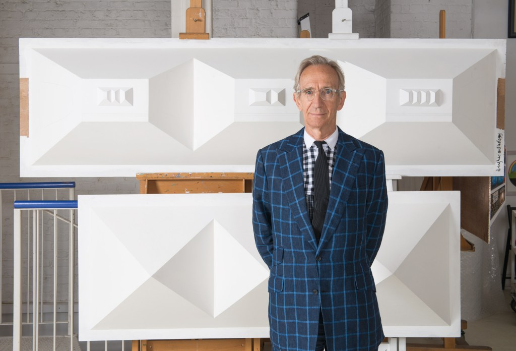 a photograph of the artist Patrick Hughes standing in front of his work in his studio in london