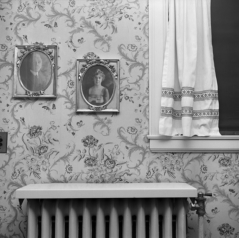 fine art print exhibition by krakow witkin featuring Shellburne Thurber, Nashua, NH: Great Grandparents' Portraits with Floral Wallpaper, black and white image of portraits on a floral wallpaper wall with a window and radiator
