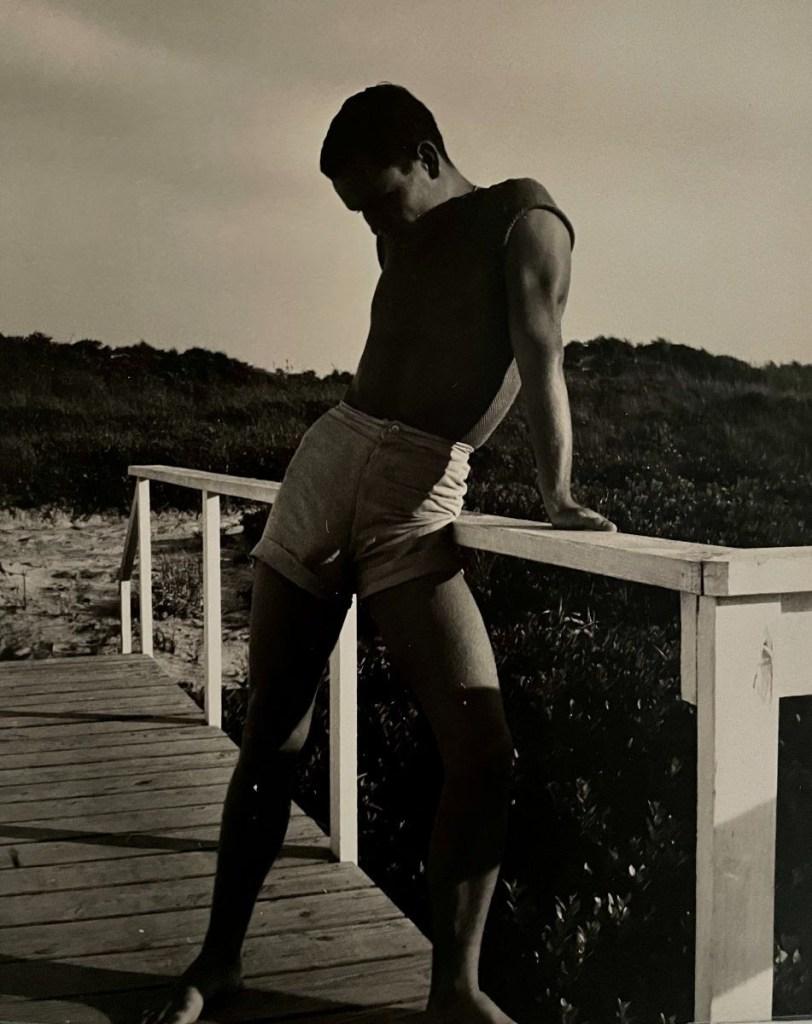 fine art print image of man in bathing suit leaning on pier by George Platt Lynes, American (1907-1955) [Chuck Howard on Boardwalk, Probably Fire Island], c.1950 Vintage gelatin silver print, 9 1/2 x 7 5/8 inches